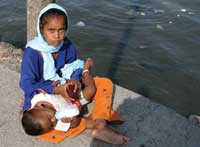 Street Life. Above, a young girl holds her infant brother while begging for money on a jetty leading out to the Haji Ali Mosque in Mumbai, India. Despite India's booming economy, half of its population still survives on less than $2 a day.