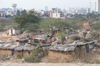 Contrast. Brick shanties border the commercial skyline of Gurgaon, India.