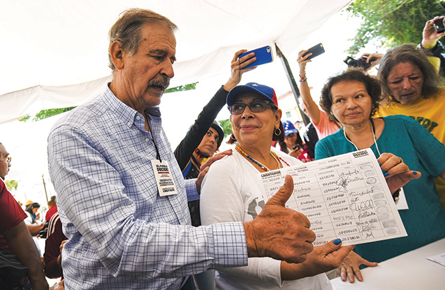 Vicente Fox, former president of Mexico, observes the voting process at a polling station during a symbolic Venezuelan plebiscite on July 16, 2017, in Caracas. The opposition alliance's unofficial plebiscite sought to challenge the legitimacy of President Nicolas Maduro's plan to rewrite the constitution. After Fox left the country, Maduro's government said he was no longer welcome to visit in yet another sign that third parties that could help broker a solution to the crisis in Venezuela are mistrusted.