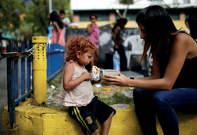 A volunteer of the Make the Difference (Haz La Diferencia) charity initiative gives a cup of soup and an arepa to a homeless child on March 5, 2017, in Caracas. As political unrest and violence continue in Venezuela, food scarcity is growing and the number of people in poverty is increasing.