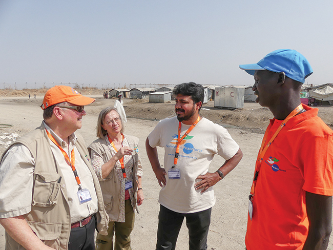 Left to right: Mel Duncan, director of advocacy and outreach for Nonviolent Peaceforce; Outi Arajärvi, a board member of the organization; Aseervatham Florington, head of the group's mission in South Sudan; and civilian protector Matthew Mathiang talk during a February 2017 visit to Bentiu, South Sudan. The United Nations recognized the practice of unarmed civilian protection when it renewed its mandate in South Sudan.