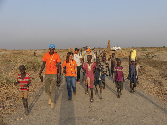 Civilian protectors Matthew Mathiang and Alona Bermejo (in orange), Aseervatham Florington the Nonviolent Peaceforce Head of Mission in South Sudan, and Mel Duncan walk with children near the Bentiu Protection of Civilians Area.