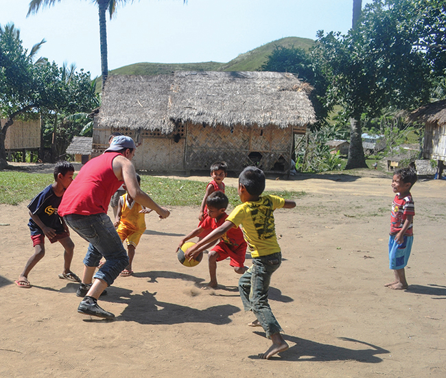 Children play with a basketball with a Nonviolent Peaceforce civilian peacekeeper in spring 2015 in Gansidan, Philippines.