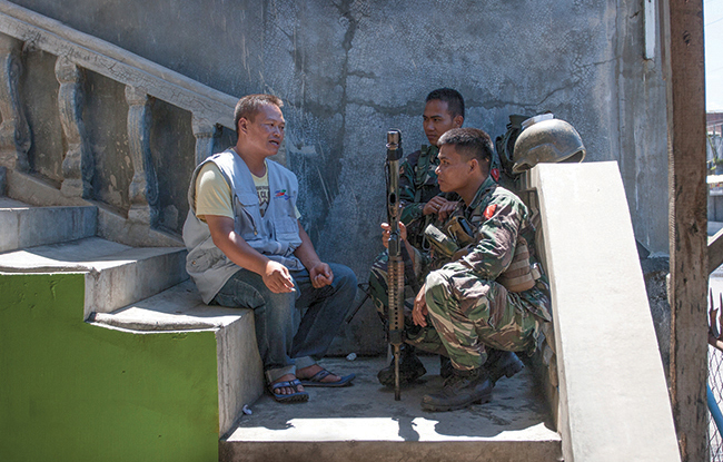 Civilian peacekeeper Badrodin Mananggolo of Nonviolent Peaceforce speaks with soldiers from the Armed Forces of the Philippines on March 26, 2013, in Malabang, Philippines.