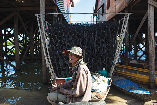 A man sits on his boat loaded with shrimp traps in Kampong Khleang.