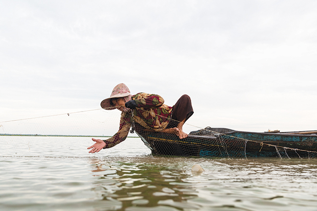 A woman looks for fish in a leaking boat in Kampong Luong.