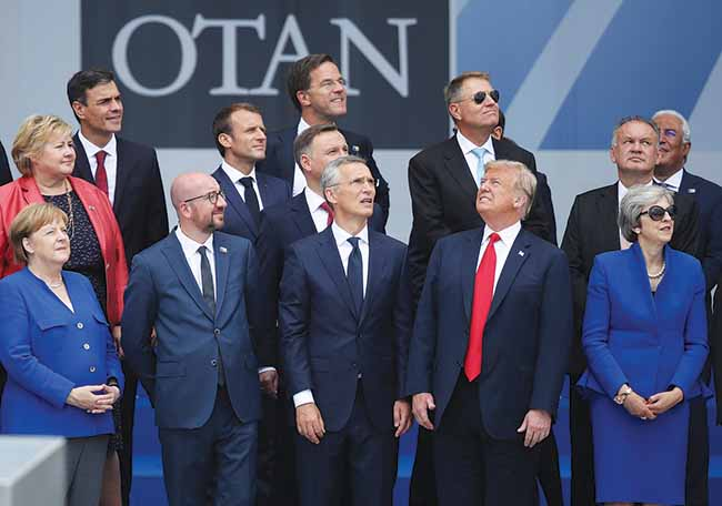 US President Donald Trump looks the other way while European leaders watch a flyover of military helicopters on July 11, 2018, during the opening ceremony of the NATO Summit in Brussels, Belgium. Trump has signaled he is against multilateralism in a way that goes beyond Bush-era rhetoric and has created friction with allies.