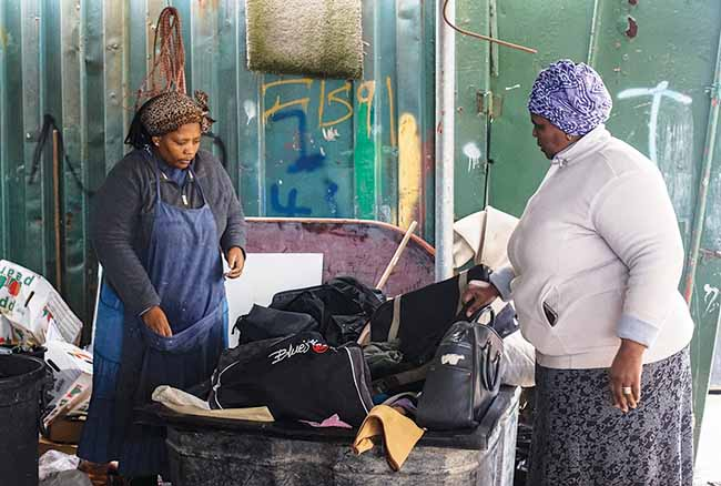 Nokwanda Sotyantya (right) speaks with Neliswa Gwetyana at the Hout Bay Recycling Cooperative in suburban Cape Town, South Africa. Sotyantya, who supports a family of 10 through her work in the waste-recycling business, said she's proud that her work helps the environment.