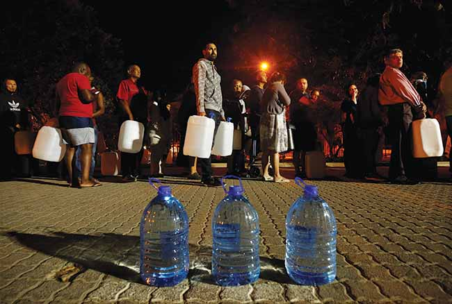 Cape Town residents line up to collect water from a spring in the suburb of Newlands on January 25, 2018, as fears over the city's water crisis grew. Climate change remains a threat to the second-largest city in South Africa.