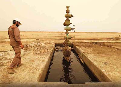 A worker walks past an oil well April 23, 2018, at the Sindbad oil field near the Iraqi-Iranian border in Basra, Iraq. Despite vast oil wealth and sustained foreign energy-sector investment, southern Iraq remains without basic services.