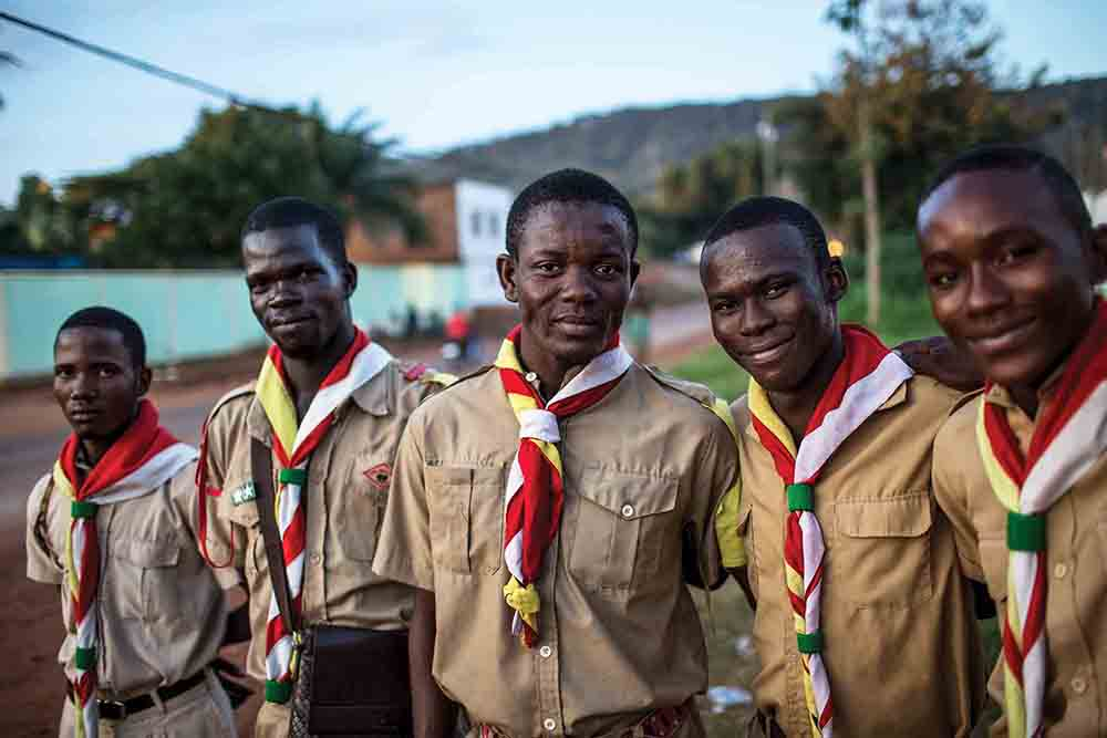 Members of the evangelical Scouting group Les Flambeaux, who have been engaged to act as security at an event, stand outside Le Complexe Scolaire International Galaxy in Bangui, Central African Republic (CAR), on August 12, 2018. Les Flambeaux and other youth Scouting organizations are frequently contracted to act as security at events in the capital.