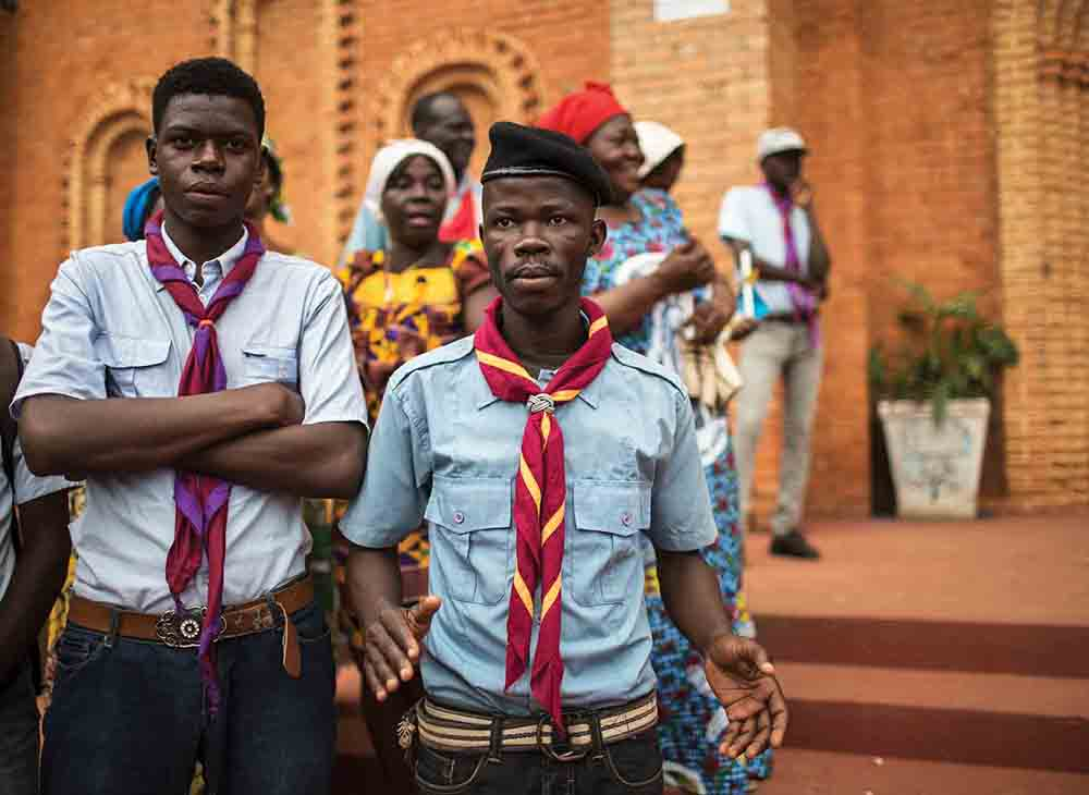 "Scouts engaged to act as security look on while Catholics gather to mark the Assumption of Mary into Heaven, on August 15, 2018, at the Notre Dame Cathedral in Bangui, CAR. ""We are warriors of peace,"" says Rony Yannick Bengai, the secretary general of the Catholic Scouts Association. ""We are here to mediate between the belligerents, to make our country livable, to stop the violence."""