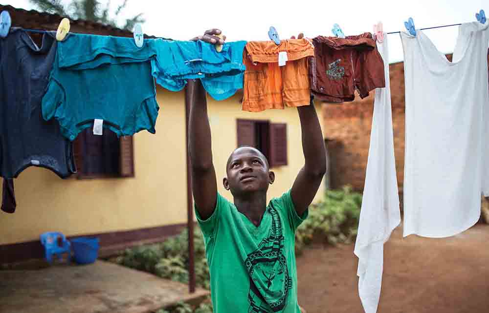 Ngoaporo Ghislain-Oxwold, a 17-year-old member of the Boy Scout organization Les Flambeaux, hangs up laundry August 13, 2018, at his home in Bangui, CAR. Members of the Scouts often learn to be responsible for household tasks like washing laundry, cooking, and cleaning­—roles that would typically be delegated to women in the family in CAR.