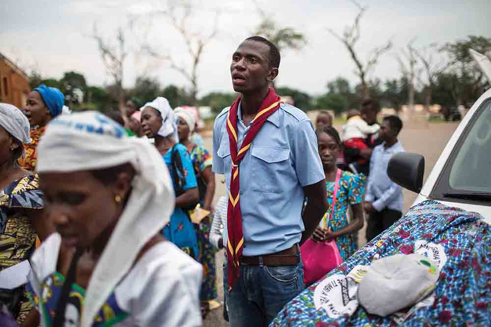 A Scout engaged to act as security sings during an event to mark the Assumption of Mary into Heaven, at the Notre Dame Cathedral in Bangui, CAR, August 15, 2018. The Scout movement in the CAR has, until recently, treated Scouting as a boys-only endeavor. But to be recognized by the international Scouting movement, girls must be allowed to participate, too.