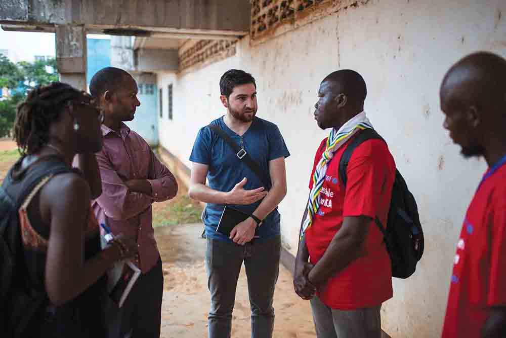 (Left to right) Amy Niang, Moussa Abdoulaye, and Simon Allison speak with Scout leaders during a youth event in Bangui, CAR, on August 11, 2018.