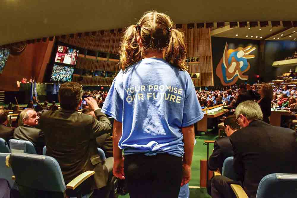 A young girl looks on at the United Nations on April 22, 2016, as dignitaries gather for a ceremony before formally signing onto the Paris Agreement on climate change. On November 22, 2018, the Climate Vulnerable Forum is holding the first zero-carbon, online gathering of heads of state to highlight enhanced commitments to the 1.5°C target. The summit also will emphasize the role women are playing in climate action.