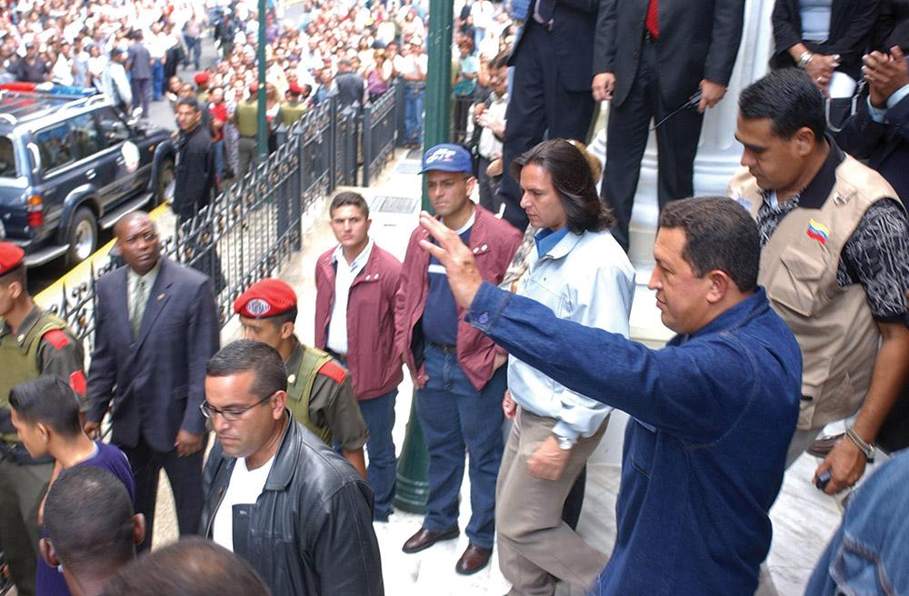 Venezuelan President Hugo Chávez (waving) exits the Teatro Municipal opera house in Caracas, May 2002.