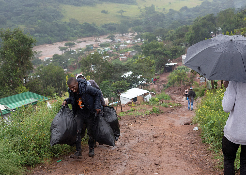People move their belongings from damaged houses after heavy rains caused flooding in Marianhill, South Africa. Extreme weather and flooding caused by climate change impede access to needed medications and treatments.