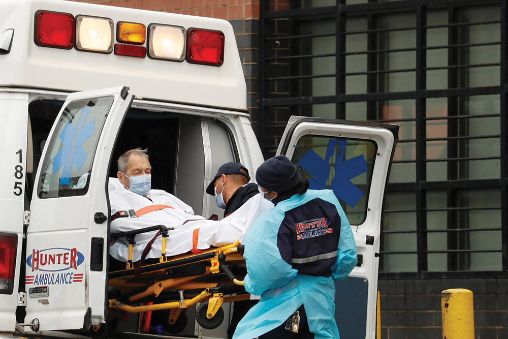 Emergency Medical Technicians load a patient into an ambulance outside the Elmhurst Hospital Center as the spread of the coronavirus disease (COVID-19) continues, in the Queens borough of New York City, April 24, 2020.